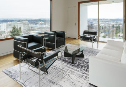 A modern living room with black and white furniture and large windows with a daytime view. Also seen are wooden floors, a balcony, and 2 doors.