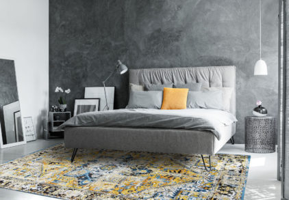 Grey king-size bed in monochromatic bedroom with mirror and white lamp above designer metal table with decorative vase