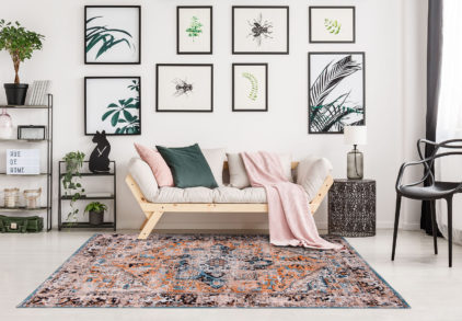 Black and white carpet and sofa with pink blanket in living room with metal chair and lamp